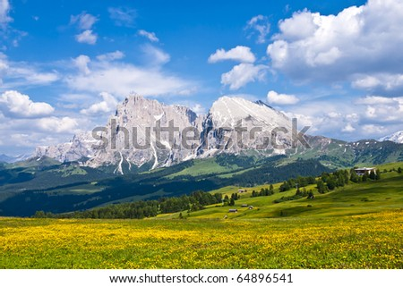 Alpine valley with the Dolomites mountains in the background. Alpe Di Siusi in Northern Italy. - stock photo