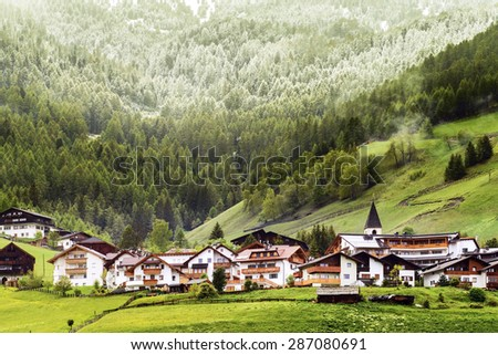 Alpine village after snowfall in the Dolomites, Italy  - stock photo