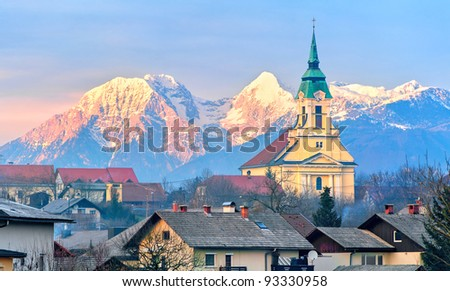 Alpine village with a church tower with snow covered mountains in background on sunset - stock photo