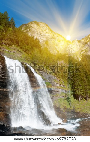 Alpine waterfall in mountain forest in sun rays under blue sky. - stock photo
