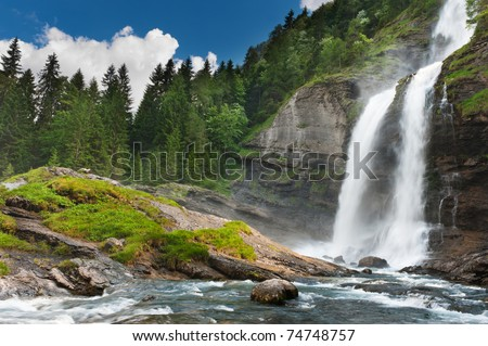 Alpine waterfall in mountain forest under blue sky.