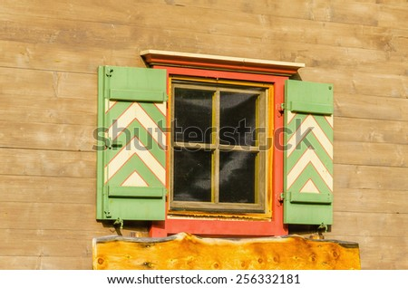 Alpine wooden bright house facade with orange window and green shutters, Zillertal, Austria - stock photo