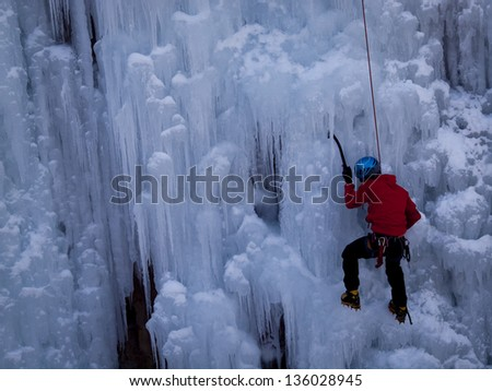 Alpinist ascenting a frozen waterfall in Ice park, Ouray. - stock photo