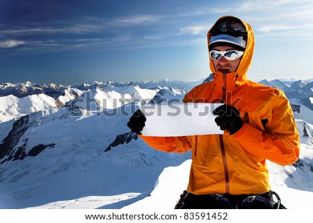 Alpinist on Monch Peak with sponsor flag, Berner Oberland, Switzerland - UNESCO Heritage - with space for text - stock photo