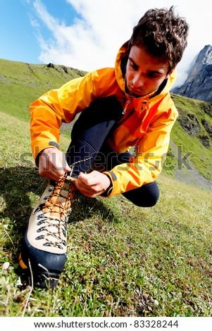 Alpinist preparing for climbing - stock photo