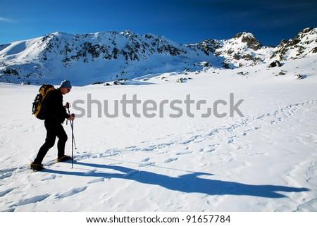 Alpinist traversing a glacier - stock photo
