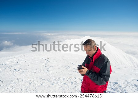Alpinist with phone in hand on the summit with majestic panoramic view of the italian Alps in winter season. Concept of sharing life moments using new technology even in hard condition. - stock photo
