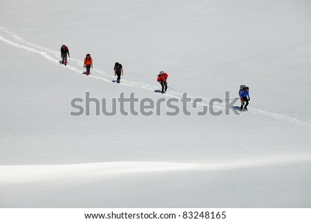 Alpinists crossing a glacier - stock photo
