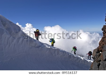 Alpinists in mountains - stock photo