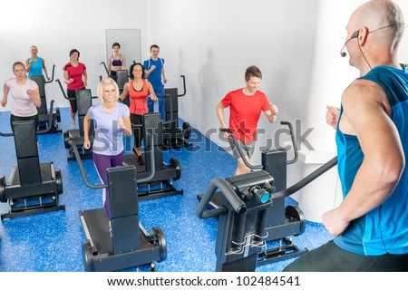 Alpinning class of young adults with fitness personal trainer - stock photo