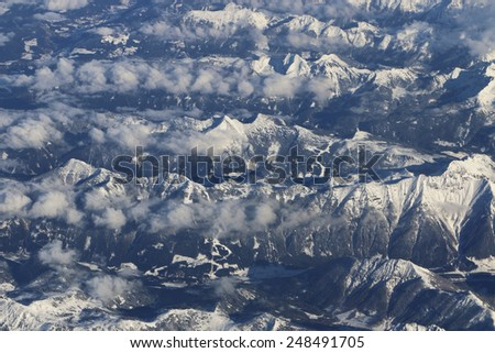 Alps, Austria. January 18, 2015. Flying over the Alps in Austria. You can see also ski a ski center among the mountains.  - stock photo