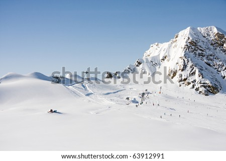 Alps mountains and ski lift in sunny winter day - stock photo