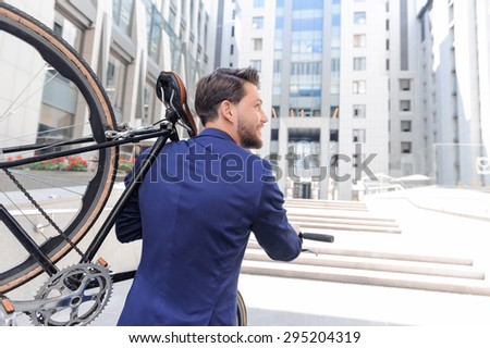 Already at work. Pleasant handsome bearded businessman holding bicycle on his shoulder and smiling while standing turned backwards. - stock photo