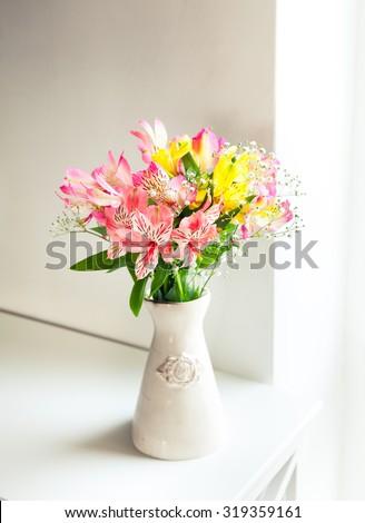 Alstroemeria flowers in vase on table - stock photo
