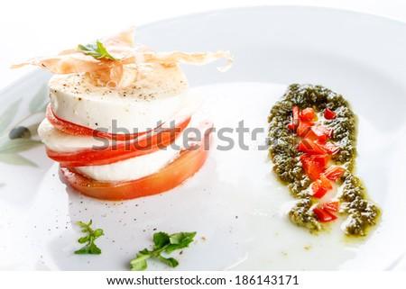 Alternating slices of mozzarella, cheese and fresh ripe tomato topped with crispy prosciutto ham served with rocket pesto for delicious Italian cuisine - stock photo