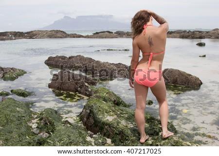 Alternative bikini beauty standing on a rock by the ocean - stock photo