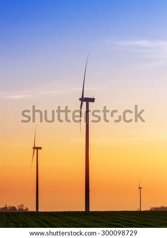 Alternative energy concept, windmills at sunset. - stock photo
