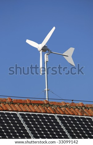 Alternative energy with solar panels and a wind engine - stock photo