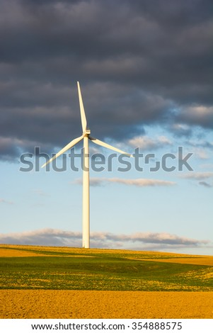 Alternative energy with wind power - three windmill silhouettes in the sunset.