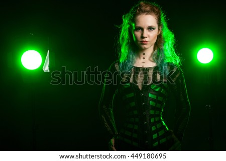Alternative fashion model in green corsait with two colored lights behind - stock photo