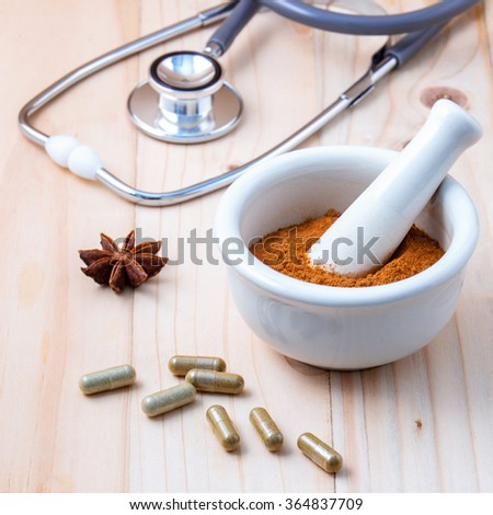 Alternative health care  Chinese herbs powder in the white mortar and herbs capsule  on old wooden background.With shallow depth of field. - stock photo