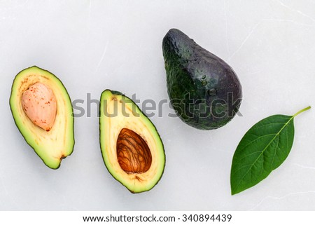 Alternative health care fresh  avocado and leaves on marble background. - stock photo