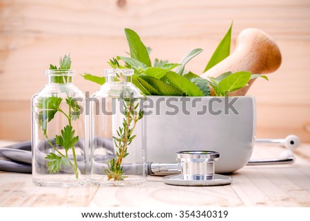 Alternative health care fresh herbal in laboratory glassware  with  stethoscope on wooden background. - stock photo