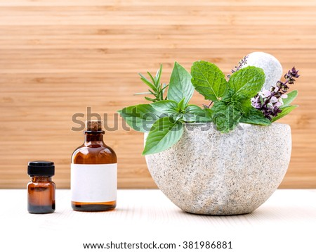 Alternative health care fresh herbs basil ,sage ,rosemary, mint  and essential oil  with mortar on wooden background. - stock photo