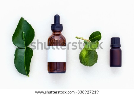 Alternative health care fresh  kaffir lime leaves and oils on marble background. - stock photo