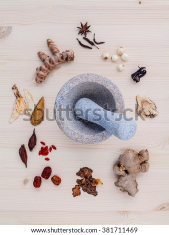 Alternative medicinal dried various Chinese herbs for healthy recipe ginseng ,goji berry ,ginger ,turmeric ,lotus seed ,star anise ,monkey apple and long pepper with mortar on wooden background. - stock photo