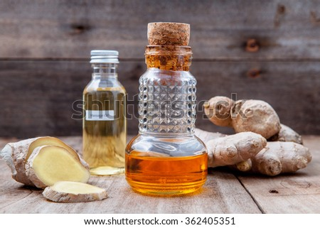 Alternative medicine and nature spas ingredients - Ginger root and ginger essential oil set up on old wooden table. - stock photo