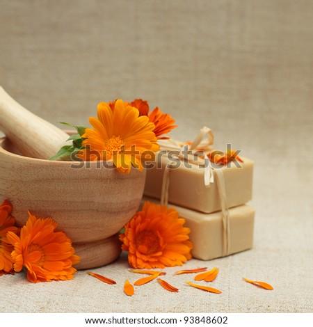 Alternative medicine background with calendula flowers and bath soap - stock photo