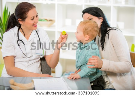 Alternative Medicine - Homeopathy.Young woman and her child at the doctor homeopaths. Treatment with herbs. Doctor gives homeopathic pills to child. - stock photo