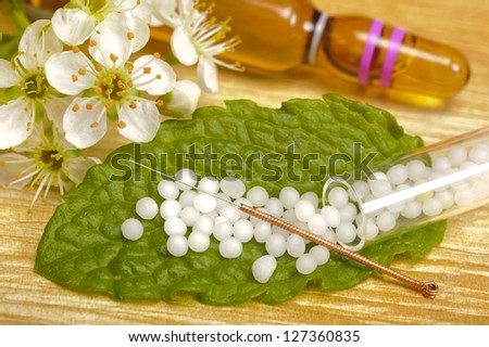 alternative medicine with globule and acupuncture - stock photo