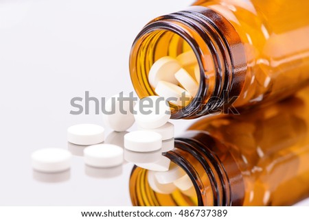 alternative medicine with herbal and homeopathic pills in brown medicinal bottle