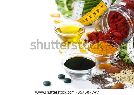 Alternative natural medicine. Dietary supplements. Spirulina, turmeric  and organic oil on white background. Superfood, detox or diet concept. Background layout with free text space. - stock photo