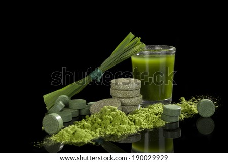 Alternative natural medicine. Green dietary supplements. Spirulina, chlorella and wheat grass isolated on black background. Green superfood, detox. - stock photo