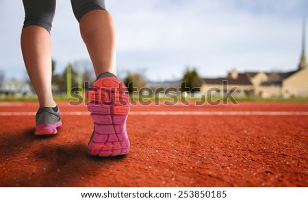 alternative perspective of woman prepping to run a track for exercise with church in the background and field in the city with an instagram filter (shallow depth of field) - stock photo