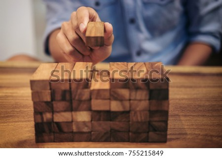Alternative risk concept, plan and strategy in business, Risk To Make Business Growth Concept With Wooden Blocks, hand of man has piling up a wooden block.