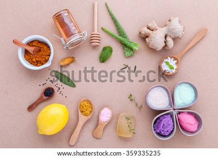 Alternative skin care and homemade scrubs with natural ingredients sage ,turmeric ,sea salt ,honey, aloe vera,lemon ,rosemary,mint and sesame set up on brown table. - stock photo