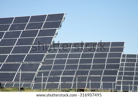 Alternative sources of producing electricity - PV meadow against the blue sky - stock photo