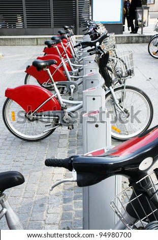 Alternative transportation: Bicycles for rent parked at a station in front of a bus stop in old european city. - stock photo