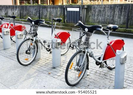 Alternative transportation: Bicycles for rent parked at a station in front of concrete wall in old european city. - stock photo