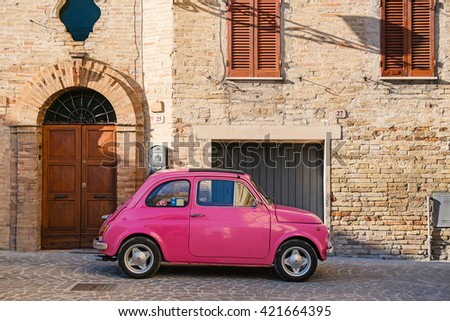 ALTIDONA, ITALY - FEBRUARY 20, 2016: Old pink Fiat Nuova 500 city car parked in a typical old village. Produced by the Italian manufacturer Fiat between 1957 and 1975. - stock photo