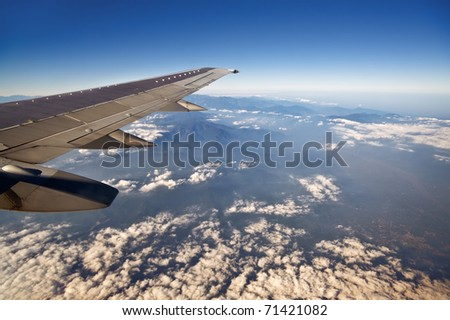 Altitude from the aircraft window to see the blue sky and white clouds view. - stock photo