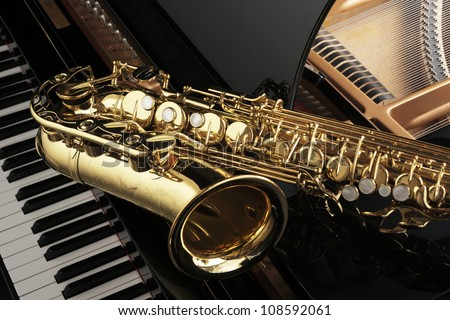 Alto saxophone on grand piano - stock photo