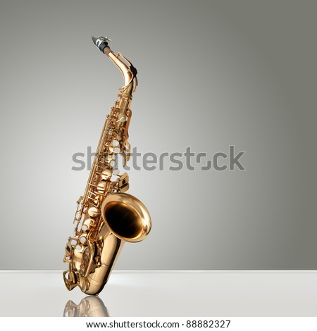 Alto Saxophone woodwind instrument over gray neutral background - stock photo