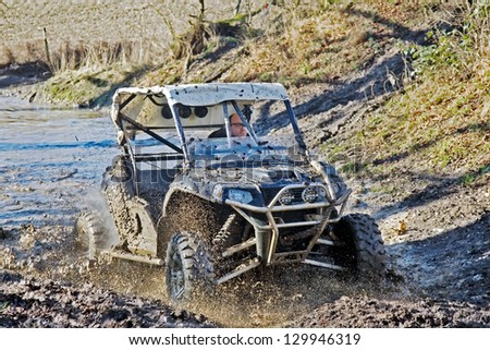 ALTON, UK - FEBRUARY 17: An unnamed driver exits a water trap at speed in his modified Polaris off road vehicle during the Nellies Dell SCOR trial event on February 17, 2013 in Alton - stock photo