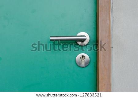 Aluminium door knob on the green door - stock photo