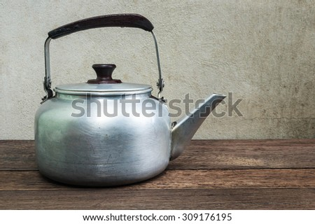 Aluminium kettle on wooden table with cement background.